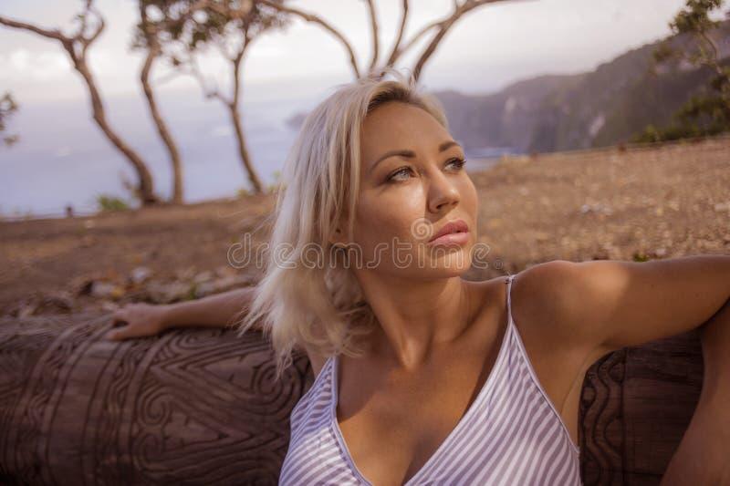 Portrait mélancolique de la jeune femme blonde attirante et belle se penchant son visage détendu sur le tronc à la forêt ou au pa photos stock