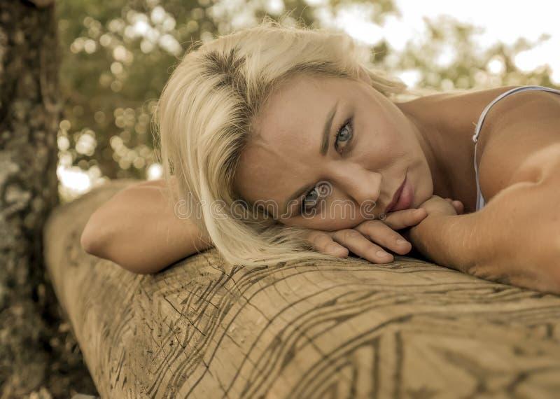 Portrait mélancolique de la jeune femme blonde attirante et belle se penchant son visage détendu sur le tronc à la forêt ou au pa image stock