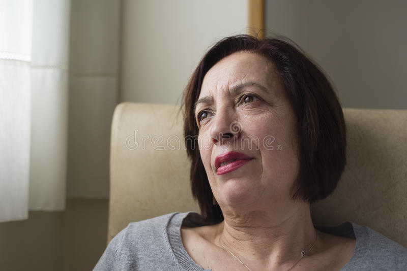 Portrait mûr de femme à l'intérieur de sa maison, photo stock