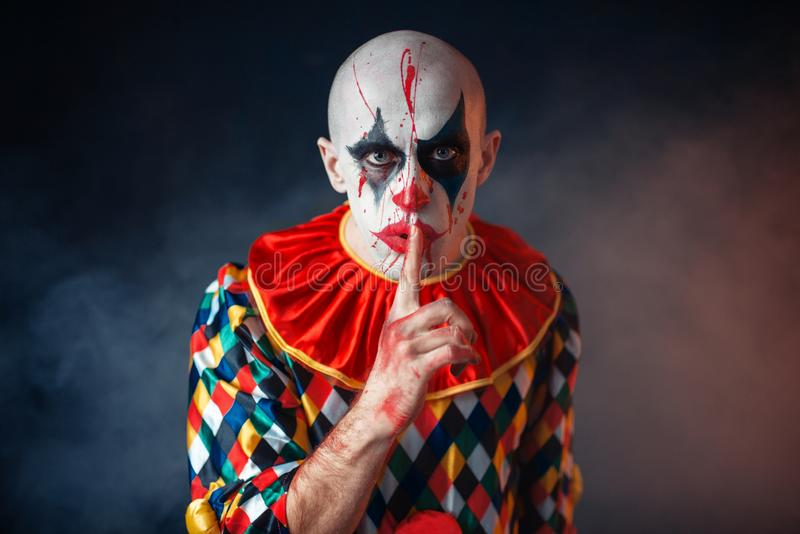 Portrait of mad bloody clown shows the quiet sign royalty free stock photo