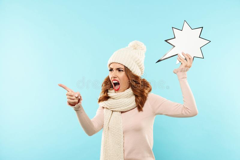 Portrait of a mad furious girl. Dressed in winter clothes holding paper speech bubble and pointing finger away isolated over blue background stock photography
