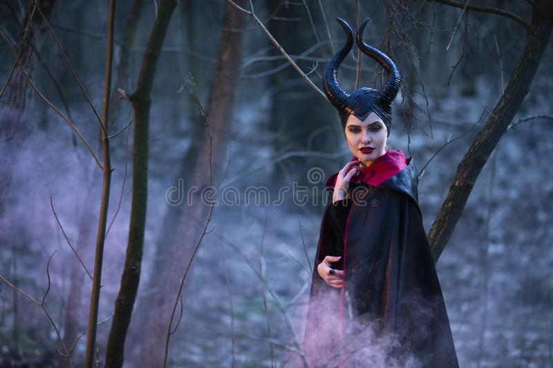 Portrait of Magical Maleficent Woman with Horns Posing in Spring Empty Forest with Smoky Background. Horizontal Image stock photos