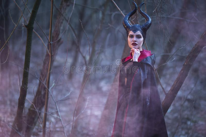 Portrait of Magical Maleficent Woman with Horns Posing in Spring Empty Forest with Smoky Background. Horizontal Image Composition stock image