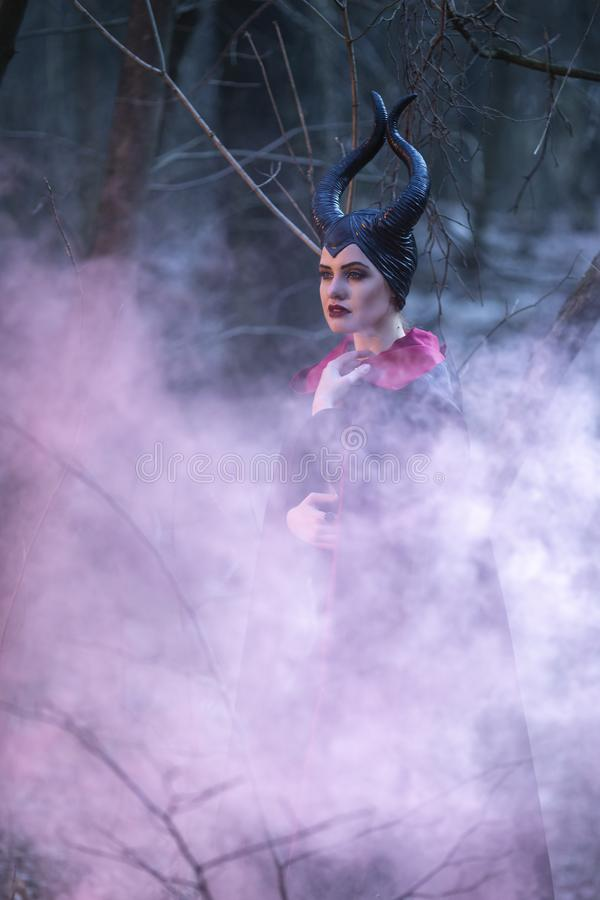 Portrait of Magical Maleficent Woman with Horns Posing in Spring Empty Forest with Smoky Background. Vertical Image Composition royalty free stock photos