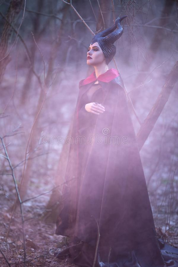 Portrait of Magical Maleficent Woman with Horns Posing in Spring Empty Forest with Smoky Background. Vertical Shot stock photography