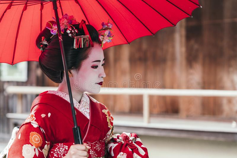 Portrait of a Maiko geisha in Gion Kyoto. Holding a red umbrella royalty free stock photo