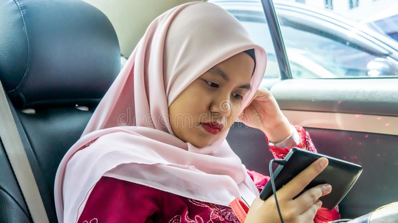 Portrait of Malay Asian muslim teenager girl using earphone and watching the smartphone royalty free stock photo