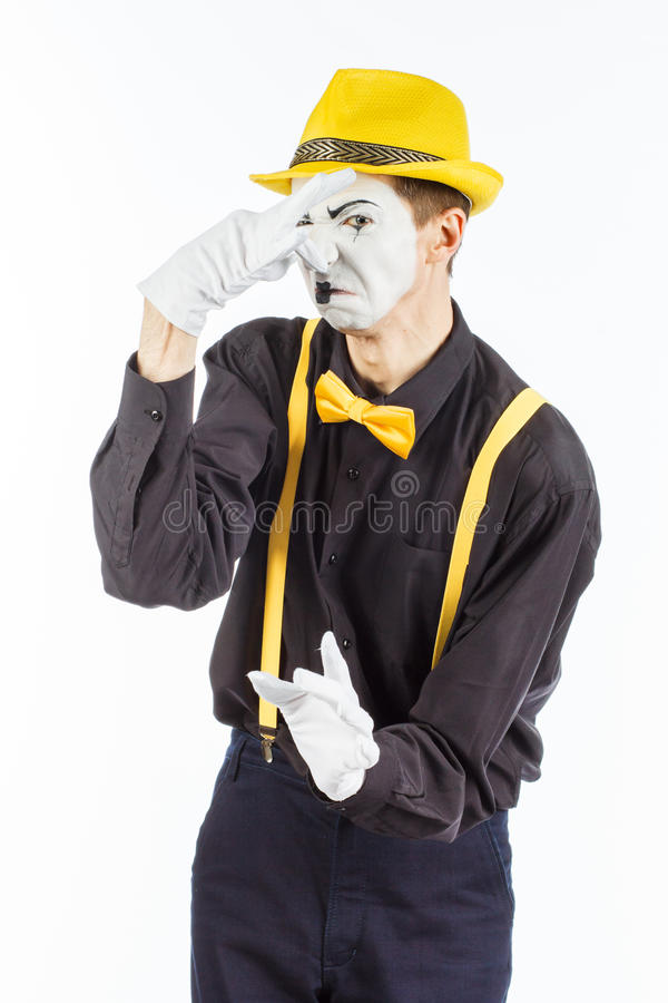 Portrait of a male actor, pantomime, covering his nose against a stock photos