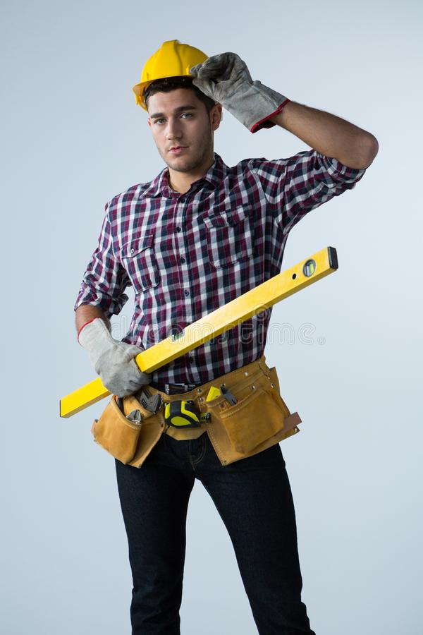 Male architect holding measuring equipment against white background. Portrait of male architect holding measuring equipment against white background royalty free stock image