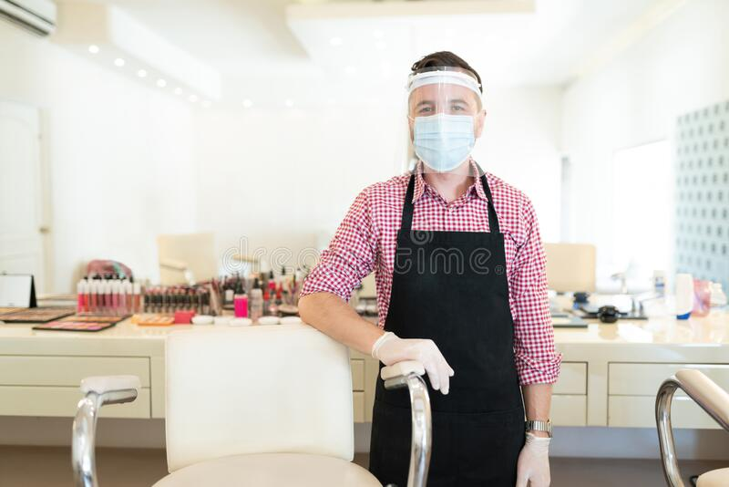 Hairdresser In Mask At Studio During COVID19. Portrait of male artist in face mask standing by chair in beauty studio during coronavirus outbreak stock photos