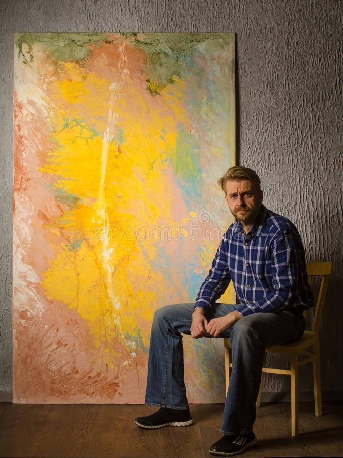 Portrait Of Male Artist sits next to his abstract painting in the Studio royalty free stock photo