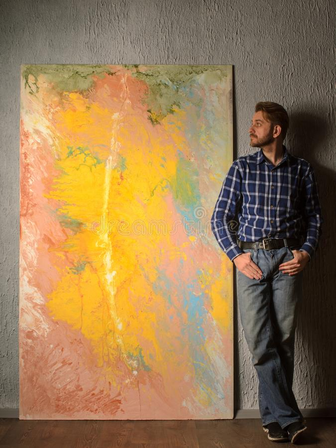 Portrait Of Male Artist standing next to his abstract painting in the Studio royalty free stock photography