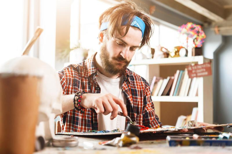 Portrait Of Male Artist Working On Painting In Studio stock photo