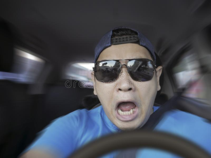Shocked Driver About To Have Accident. Portrait of male Asian driver shocked and panic about to have crash accident, zoomed motion blur defocus concept royalty free stock photo