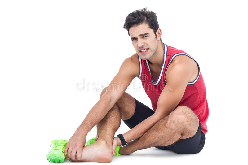 Portrait of male athlete with foot pain on white background. Portrait of male athlete with foot pain on isolated white background stock images