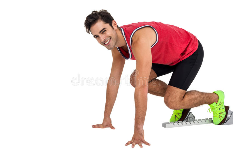 Portrait of male athlete in ready to run position. Happy male athlete in ready to run position on white background royalty free stock image