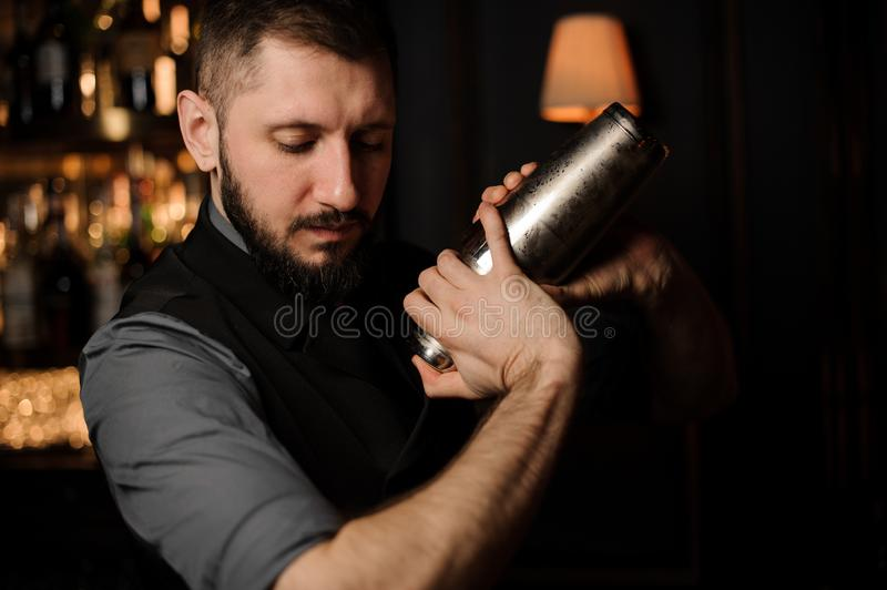 Portrait of male bartender with shaker in his hands. Portrait of male bartender with beard holding shaker in his hands stock photos