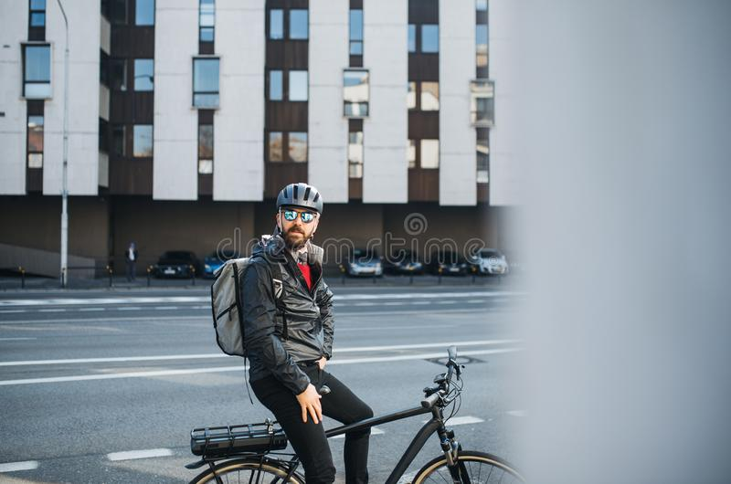 Male bicycle courier with backpack and sunglasses delivering packages in city. A portrait of male bicycle courier with backpack delivering packages in city stock photos