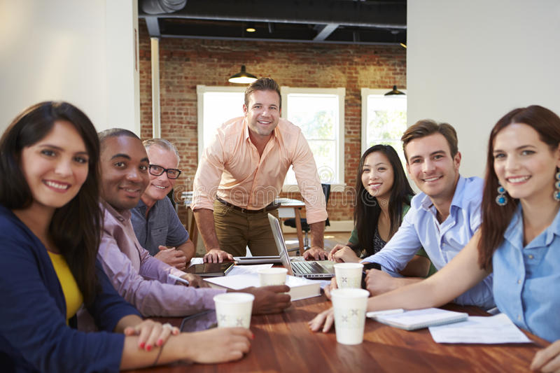 Portrait Of Male Boss With Team In Meeting stock photography