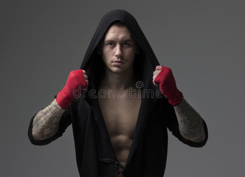 Portrait of a male boxing fighter in sportswear. Portrait of a male boxing fighter looking at camera in sportswear and looking serious and aggressive stock photos