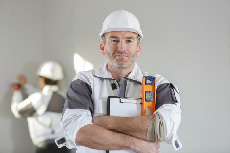 Portrait male builder with spirit level and electric drill stock image
