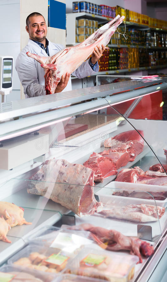 Portrait of male butcher in kosher section at supermarket. Portrait of positive european male butcher in kosher section at supermarket royalty free stock photography