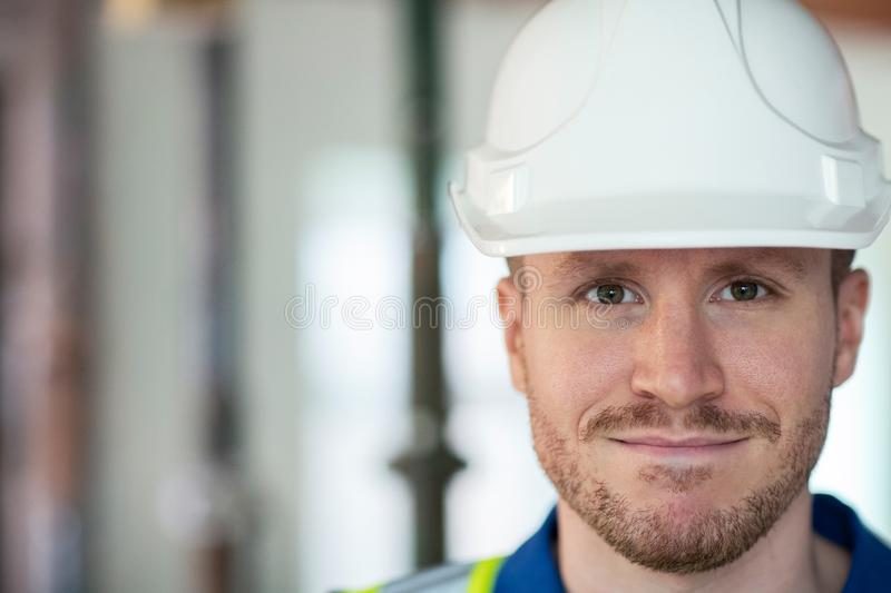 Portrait Of Male Construction Worker On Building Site Wearing Hard Hat. Male Construction Worker On Building Site Wearing Hard Hat royalty free stock photo