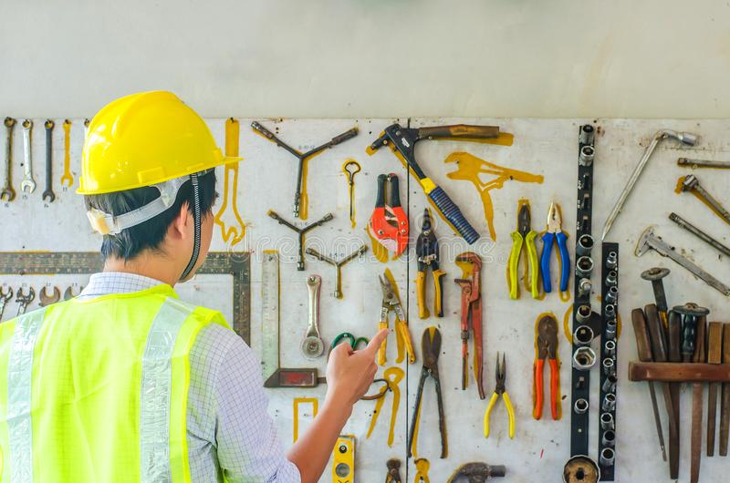 Portrait of a male construction worker in the helmet choosing the many different rusty old tools hanging on a wall stock photography