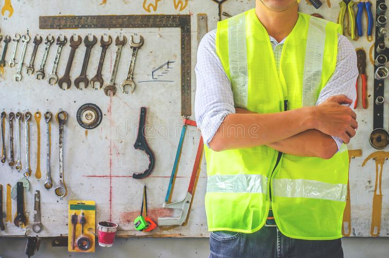 Portrait of a male construction worker in the helmet near the many different rusty old tools hanging on a wall stock photo