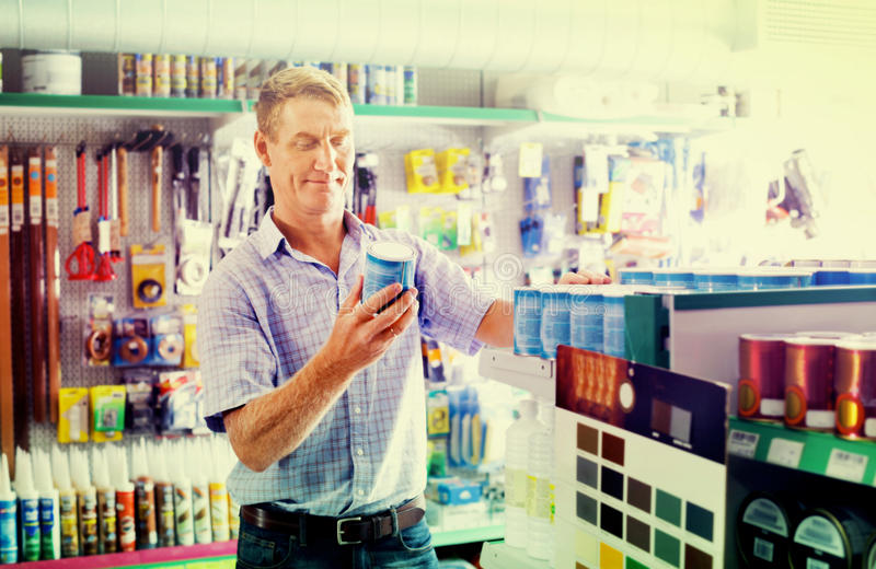 Portrait of male customer selecting paint can in housewares department stock photos