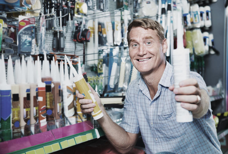 Portrait of male customer selecting sealant bottle i stock photo
