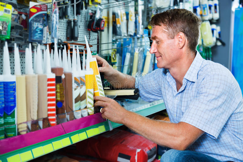 Portrait of male customer selecting sealant bottle i royalty free stock photography