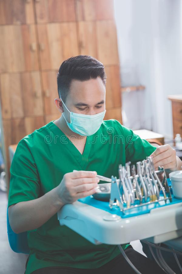 Male dentist prepare. Portrait of male doctor in green costume wearing medical mask sitting on dentist chair in dental clinic stock image