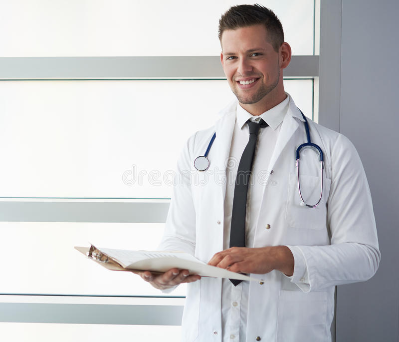 Portrait of a male doctor holding his patient chart in bright modern hospital stock photos