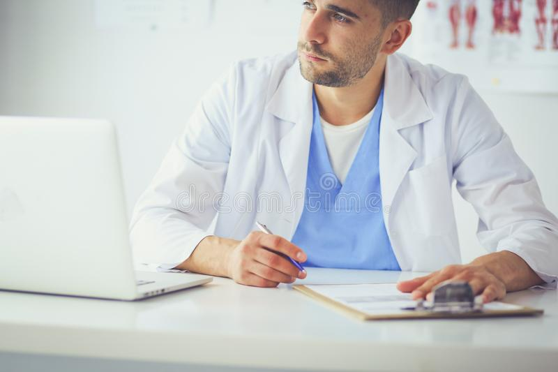Portrait of a male doctor with laptop sitting at desk in medical office stock image