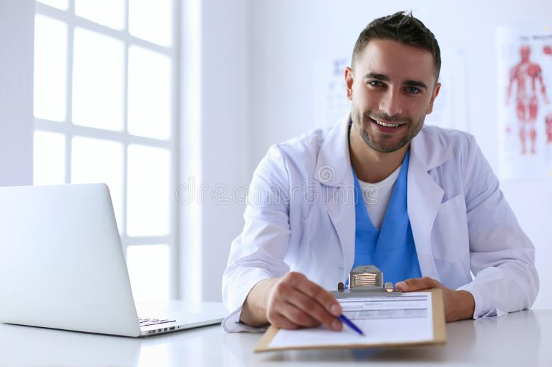 Portrait of a male doctor with laptop sitting at desk in medical office stock images