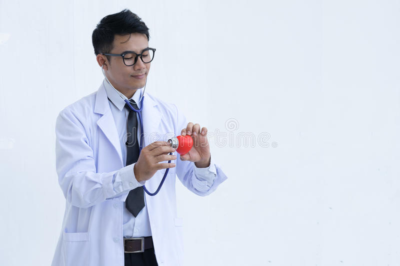 Portrait of male doctor with red heart and stethoscope royalty free stock photography