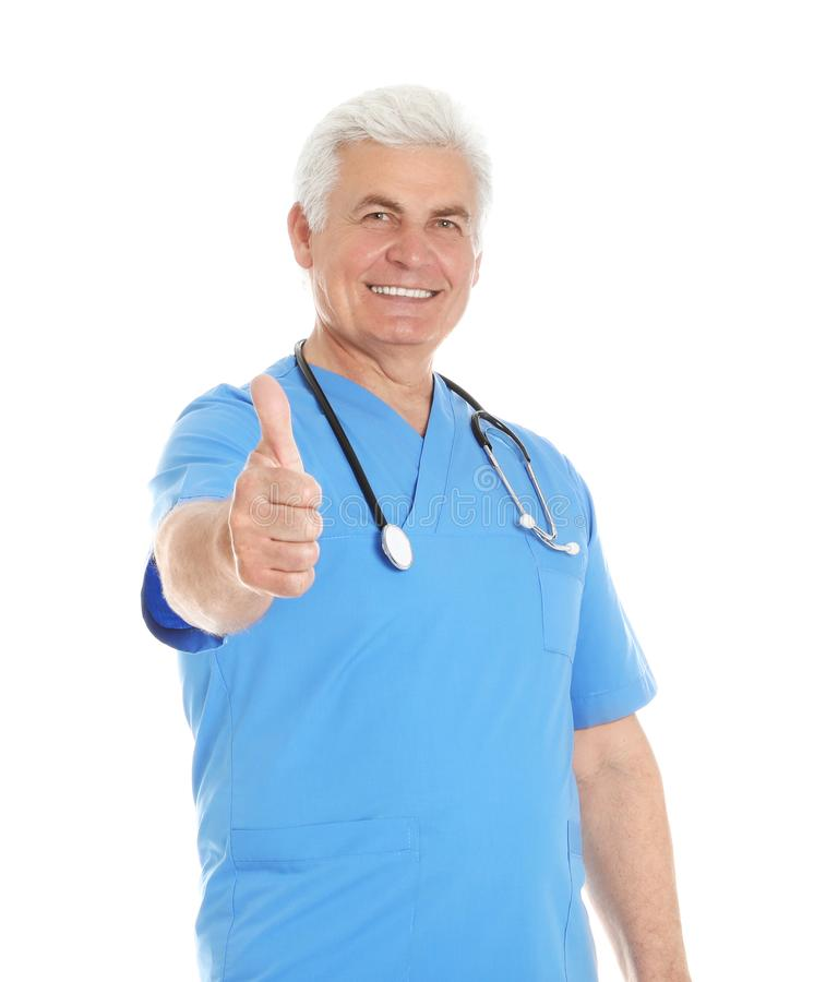 Portrait of male doctor in scrubs showing thumb up isolated on white stock image
