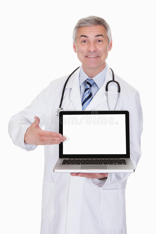 Portrait Of Male Doctor Showing Laptop. Over White Background royalty free stock photo