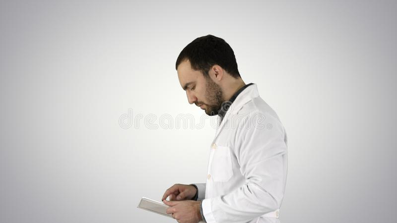 Portrait of male doctor walking and using digital tablet on gradient background. royalty free stock image