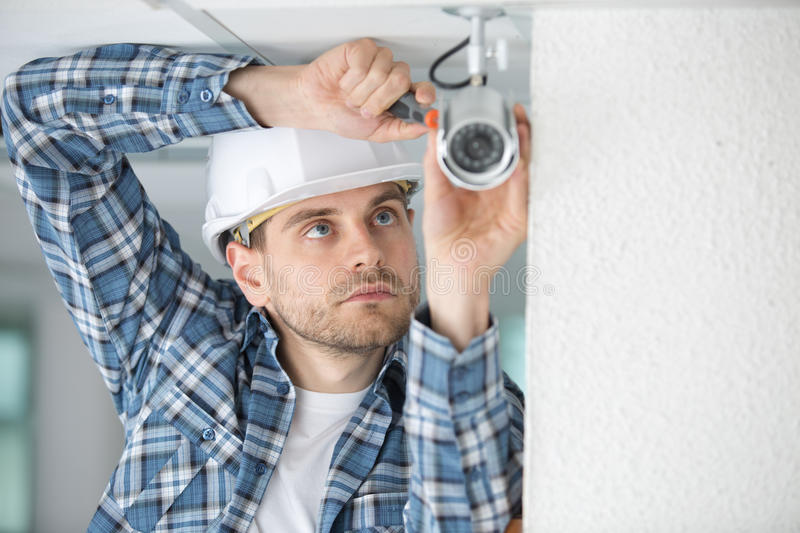 Portrait male electrician fixing light on ceiling stock image