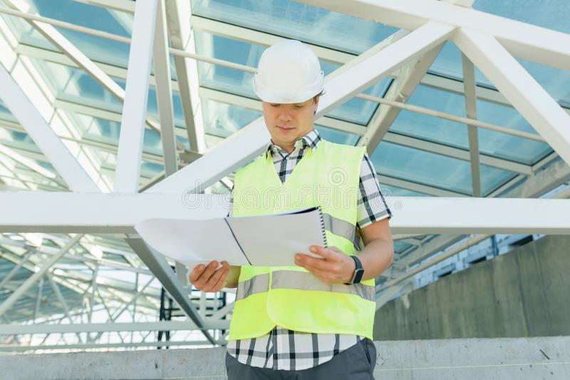 Portrait of male engineer at construction site, builder looks at blueprint. Building, development, teamwork and people concept stock photo