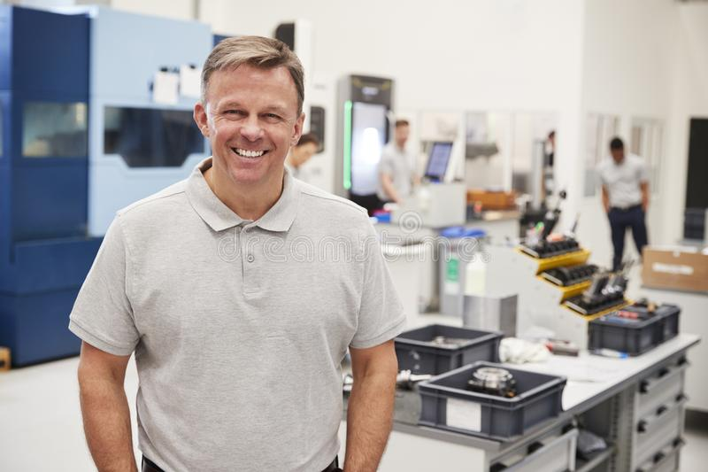 Portrait Of Male Engineer On Factory Floor Of Busy Workshop royalty free stock images