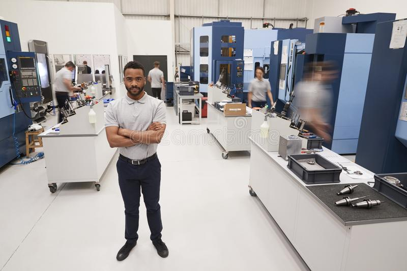 Portrait Of Male Engineer On Factory Floor Of Busy Workshop stock images