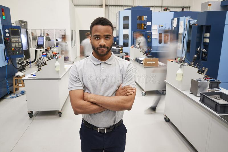Portrait Of Male Engineer On Factory Floor Of Busy Workshop stock photography