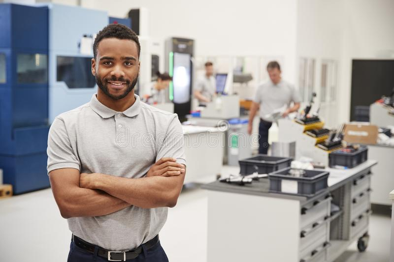 Portrait Of Male Engineer On Factory Floor Of Busy Workshop stock photos