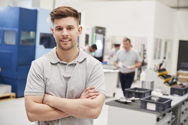 Portrait Of Male Engineer On Factory Floor Of Busy Workshop stock photo