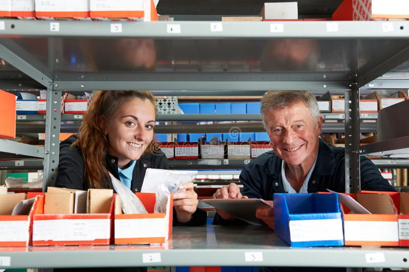 Portrait Of Male Engineer With Female Apprentice Checking Stock Levels  Using Digital Tablet. Male Engineer With Female Apprentice Checking Stock Levels Using royalty free stock images