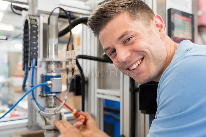 Portrait Of Male Engineer Working On Machine In Factory. Portrait Of Male Engineer Servicing Machine In Factory royalty free stock photos