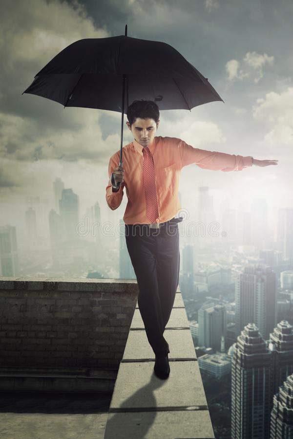 Male entrepreneur with umbrella on rooftop. Portrait of male entrepreneur holding an umbrella while walking on the rooftop royalty free stock images
